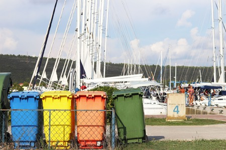 Multi-colored plastic garbage cans for waste sorting are on the quay in the marina against the backdrop of sailing yachts. Cleaning the yacht after the charter. Recycling and garbage disposal.