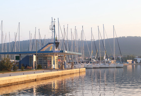 Gas station in the Mediterranean marina on the background of sailing yachts in the rays of sunset. Refueling boats and fishing boats. Infrastructure of the Adriatic port. Saturday charter conditions.