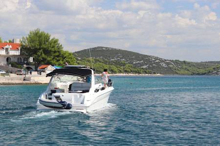 The company of friends on a small motor yacht sails along the coast near a small Mediterranean town. Rest on the water in the paradise. Cruise on a charter boat in the Croatian Riviera. Dalmatian isla