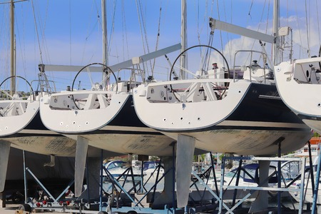 Same yachts stand in a row on the dry parking in the marina on a sunny summer day. Device sailing vessel below the waterline. Stern sports boat. Mediterranean city. Preparing for the sailing charter.