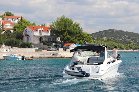 The company of friends on a small motor yacht sails along the coast near a small Mediterranean town. Rest on the water in the paradise. Cruise on a charter boat in the Croatian Riviera. Dalmatian isla.