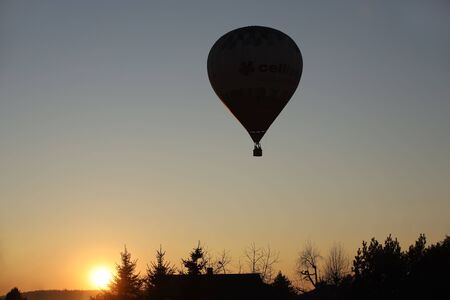 Flight in a balloon in the rays of the evening sunset.