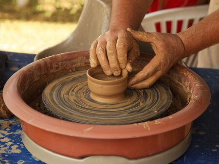 Hands of a potter sculpt clay dishes on a pottery wheel. Folk craft for making dishes. Creation of a ceramic product. Teaching ancient craft. Utensils for everyday life. History of folk art. Dirty han