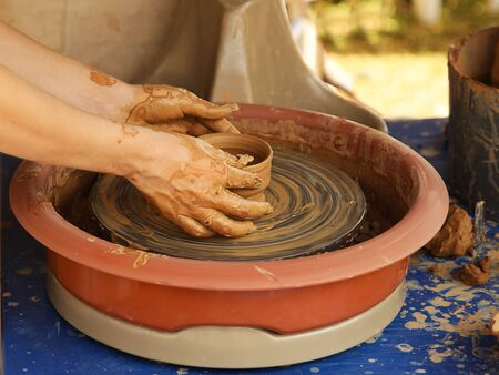 The delicate hands of a potter woman sculpt clay dishes on a potters wheel. Folk craft for making dishes. Creation of a ceramic product. Teaching ancient craft. Utensils for everyday life.