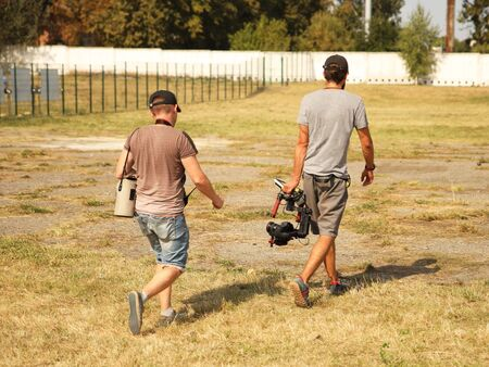 Bloggers videographer and photographer go with the camera on the stabilizer on a fenced field with grass. Modern technologies for the production of video content. Travel vlogers with gimbal in search.