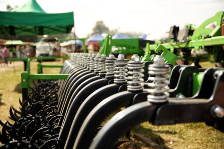Spring shock absorbers cultivator. A fragment of agricultural machinery for loosening plowed fields. Mechanization of labor in the farm. Mechanical engineering for growing plants in the open field. 免版税图像