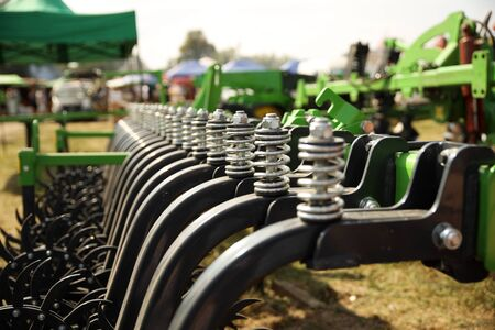 Spring shock absorbers cultivator. A fragment of agricultural machinery for loosening plowed fields. Mechanization of labor in the farm. Mechanical engineering for growing plants in the open field. Stok Fotoğraf