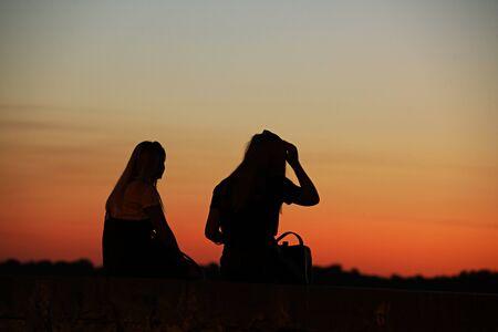 Die dunkle Macht zweier Mädchen vor dem Hintergrund eines purpurroten Sonnenuntergangs. Ein Spiel von Farben und Dunkelheit. Fotografieren im Dunkeln mit wenig Licht. Am Abend entspannen sich die Freundinnen romantisch. Standard-Bild