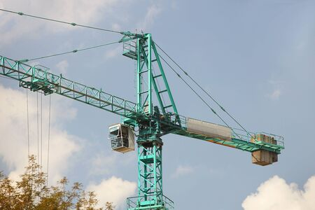 Tower cranes work during the construction of a multi-story building. New apartments for residents and premises for offices. Risky work at height. Lifting heavy building materials. City development.