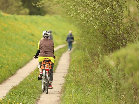 An old gray-haired woman rides a bicycle among the greens. A healthy and active part of life. Ecological transport for the population. Free time for retirement. Movement in space. Sports for the elder Stockfoto