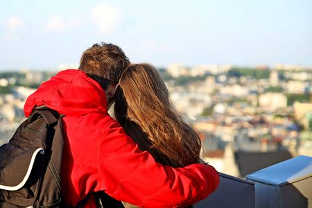 A guy in a red jacket is standing in an embrace with a long-haired girl. A young couple at the observation deck of the Lviv City Hall peers into the panorama of the ancient city. Couple in love.