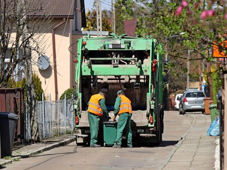 Collection and transportation of household garbage by utility workers on a flowering street. Monitoring the environmental situation in cities. Recycling human waste. Territory cleaning. Garbage remova. Stockfoto