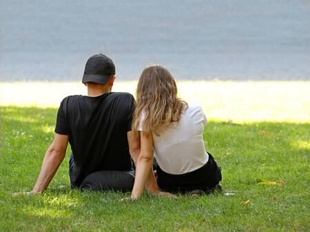A guy with a girl sitting on the grass by the sea. Loving couple on a romantic date in nature in summer. The relationship between a man and a woman. Weaving hands. Staying together. Love between teens.