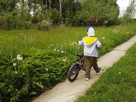 A little boy rides a children's bike along a path amidst fresh greenery. Joyful childhood. Striving forward to a dream. Physical activity at a young age. Children's toys for comprehensive development. 版權商用圖片