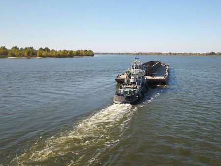 A tugboat ship pushes a barge upstream of the river to transport bulk materials. Aerial photography with a quadcopter or a drone. Panorama of the Dnieper - the main water transport artery of Ukraine. Foto de archivo