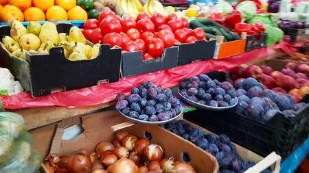 Een verscheidenheid aan groenten en fruit liggend op een marktbalie te koop door een klant. Handel in landbouwproducten. Nitraten en pesticiden. Genetisch gemanipuleerd voedsel. Boerderij fruit. Vezels en vitamines.
