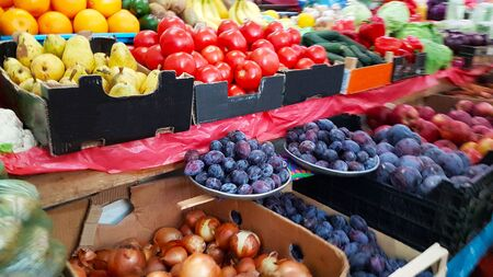 Une variété de légumes et de fruits se trouvant sur un comptoir de marché à vendre par un client. Commerce de produits agricoles. Nitrates et pesticides. Nourriture génétiquement modifiée. Fruits de la ferme. Fibres et vitamines.