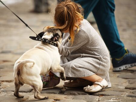 A little girl in stylish clothes plays on the street with a pug dog. The joy of communicating with pets. Parenting sensitive to your favorite pets. The love of animals for owners and children. Lovely.