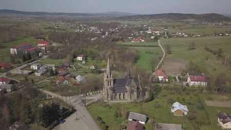 Panorama of a small European village with a Christian Catholic church in the center. Farms among green picturesque hills Cieklin, Poland