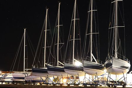 Stationnement à sec de nuit des yachts dans la marina croate ACI de la ville de Jazira. Lumières brûlantes du port méditerranéen du soir avec voiliers et bateaux de pêche. Crépuscule sur la Rivie Adriatique