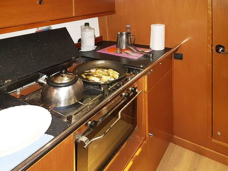 Yacht Bavaria caribian cruiser. Maritimes kitchen. Kabuz. Frying fish in the galley of a sailing yacht. A healthy diet and a compelling lifestyle for active people at sea. Omega acids from animals. Stockfoto