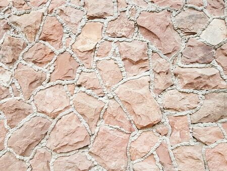 Ancient medieval stone masonry. Texture of a fragment of a wall of an old structure. A background for design and creative work. Decoration and exterior decoration of the building. Construction works.