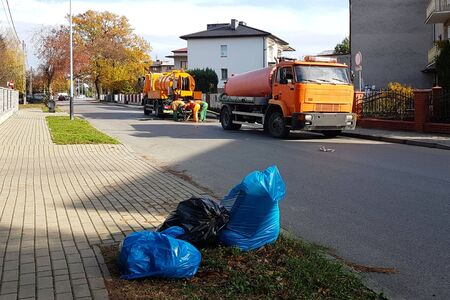 Sewage clearing by special technical means on the streets of a small European town. Orange cars and municipal workers clean the city from debris and dirt. Infrastructure.