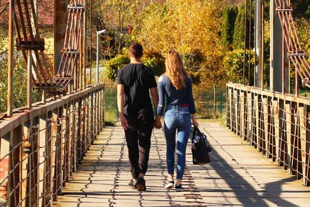 Young couple:the guy and the girl walk on the bridge in the fall holding hands. Romatic relations between a man and a woman. The manifestation of love between people. Walk in the fresh air. Common way. Imagens