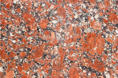 The background of polished granite in red black shades. A background for design and creative work. Decoration and exterior decoration of the building. Construction works.