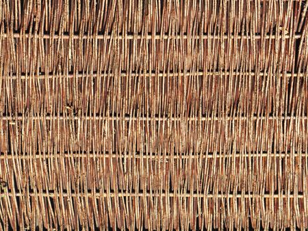 Weaving from willow branches. Background for the design of natural components. Handwork. Use of natural resources. Fence from tree branches. Environmentally friendly raw materials for the manufacture. Stock Photo