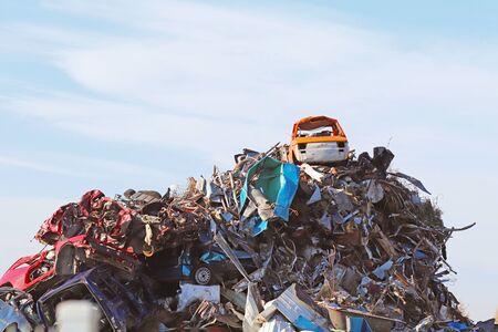Crane picking up a car in a junkyard.