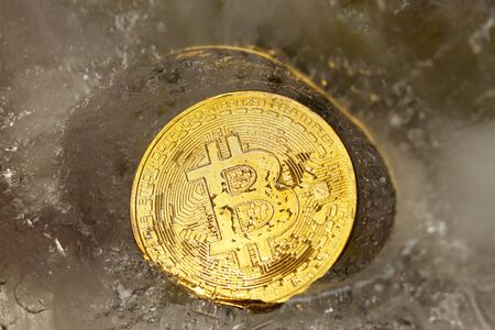 A bitcoin gold coin frozen in ice covered with drops of moisture iridescent in the rays of light. The freezing of financial assets. Fall and growth of online business. Cryptocurrency rate. Imagens