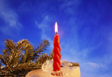 Christmas and New Year decoration. Burning red candle with ice on the background of tree branches and blue sky. Happy mood on a family holiday. Artistic design for the winter holidays.