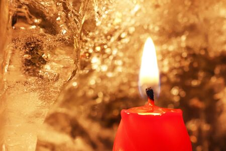 Christmas and New Year decoration. Burning red candle with ice on a dark background. Happy mood on a family holiday. Artistic design for the winter holidays. Warm light. Imagens