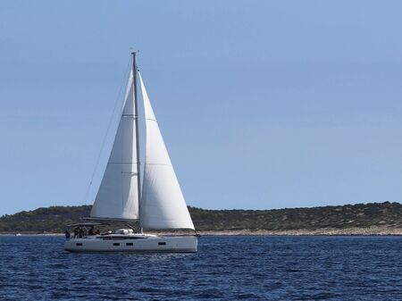 A modern cruise sailing yacht with a Bermuda sloop-type rig goes past the green coast of the Croatian Riviera on a sunny summer day. Adriatic Sea of the Mediterranean region. District of Dalmatia. Banco de Imagens