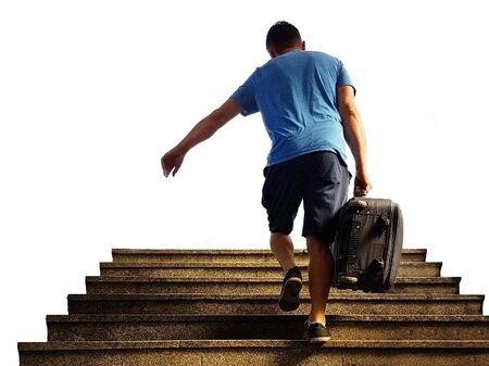 A young guy with a road suitcase climbs the stairs from the underpass isolated on a white background. The thief runs off with stolen luggage. Catch on transport. Anxiety at the train station.