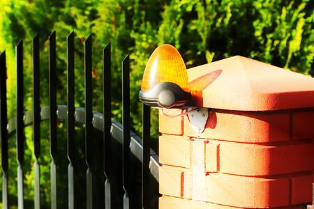 Orange room alarm light located on a brick fence post. Intercom apartment building at the entrance to a private protected area. Hazard alert. Intercom for door curtain. Property Protection and Securit. Stock Photo
