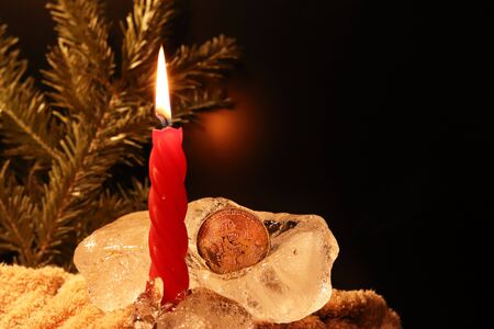 Christmas and New Year decoration. Burning red candle with ice on a dark background. Happy mood on a family holiday. Artistic design for the winter holidays. Warm light.