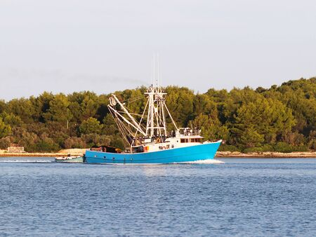 The fishing vessel for squid extraction returns in the early morning sailing past the green shore. Catch of cephalopods in the Adriatic Sea of the Mediterranean region. District Dalmatia of Croatia.