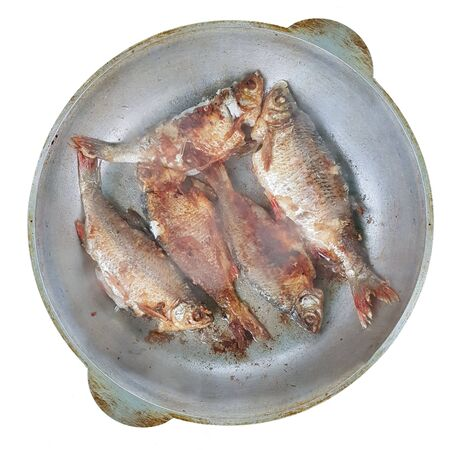 Top view of the river fish, which is fried in a round pan. Cooking in the field. Popular cuisine for travelers and men. Catch fishing isolated on white background. Protection of water management.