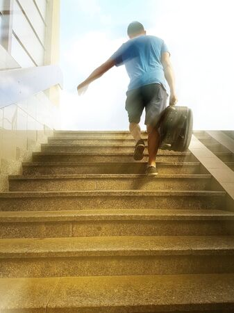 A young guy with a travel suitcase runs up the stairs from the underpass. The thief escapes with stolen carry-on luggage. Catch on transport. Turmoil at the vogal. The path to a better life: freedom.