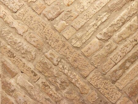 Masonry on the floor of marble brick in warm tones. Texture and background for design and decoration. Natural building material. The work of a mason. Ancient solid buildings. historical technologies of road construction.