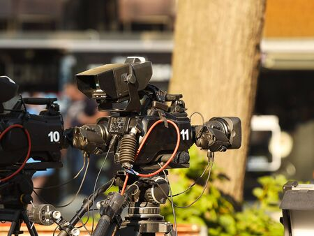 Professional movie cameras on the set among other equipment. Production of a film or report on the streets of the city. Documentary and artistic shooting. Japanese electronics. Videographer and high t