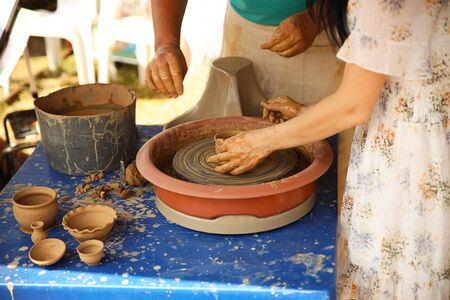 The delicate hands of a potter woman sculpt clay dishes on a potter's wheel. Folk craft for making dishes. Creation of a ceramic product. Teaching ancient craft. Utensils for everyday life. History.