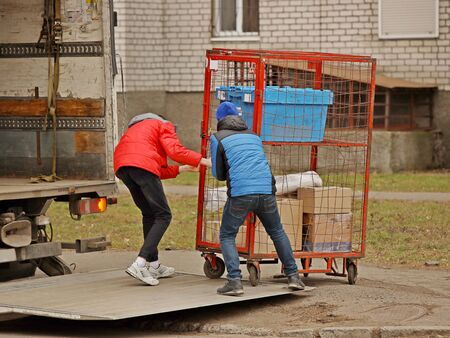 Two workers are loading a trolley with a cage for transporting goods onto the lift of a truck for transportation. Automation of manual work of loaders. Elevator platform on the rear side of the road trailer body. Raise up.