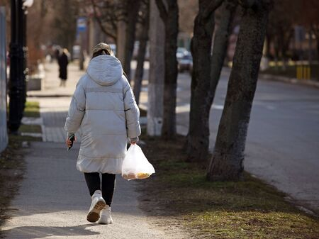 A woman with a package is walking along the sidewalk in the rays of sunlight. Pedestrian on a city street. Everyday life of a woman mistress at home. Shopping trip to the store. Using a plastic bag on