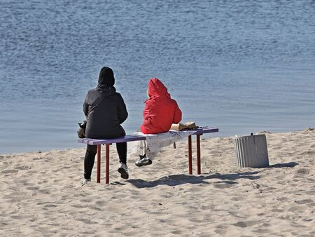 An adult with a child are sitting on a bench on a sandy beach by the sea or river. Walks in the open air. Parenting a child. The infrastructure of the city beach and places for recreation. 版權商用圖片