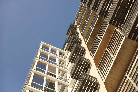 Lviv, Ukraine - 3 4 2020: Facade of a tall multi-storey modern house with balconies and large glass windows. Design of modern architecture. Top view from the bottom. Modern city architecture Editorial