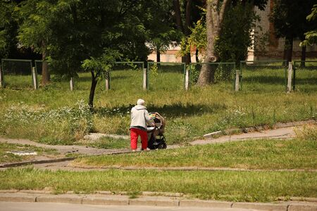 An elderly woman walks with a pram among the summer greenery. A governess is nursing a child on the street. Raising children zorovym and seasoned. Baby sleep in the fresh air. Socialization of older.