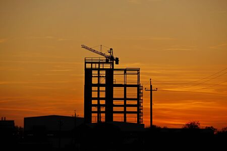 The skeleton of the construction of a skyscraper under construction with a tower crane against the background of an orange sky with the setting sun. Romantic landscape of a natural phenomenon.Building. Stock Photo